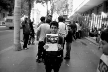 Bambino rom con cartello di protesta davanti l'assessorato alle Politiche Sociali (Foto di Chiara Rossi)