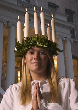 """''Lucia di Svezia"""" con una corona di sette candele e vestita di una tunica bianca...raccoglie le offerte e i doni da distribuire ai poveri e ai bisognosi in occasione delle feste natalizie"""